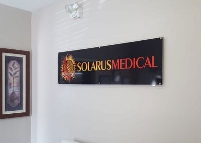 Solarus Medical logo vinyl print adhered to clear acrylic attached to office wall with stand-offs