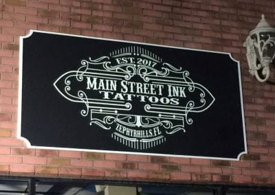 Black and white routed HDPE board with Main Street Ink Tattoos logo