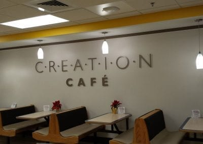 Gold cut metal letters attached to a wall saying Creation Cafe
