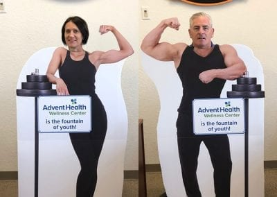 Sue and Mike posing behind cut outs of a fit woman and a fit man.
